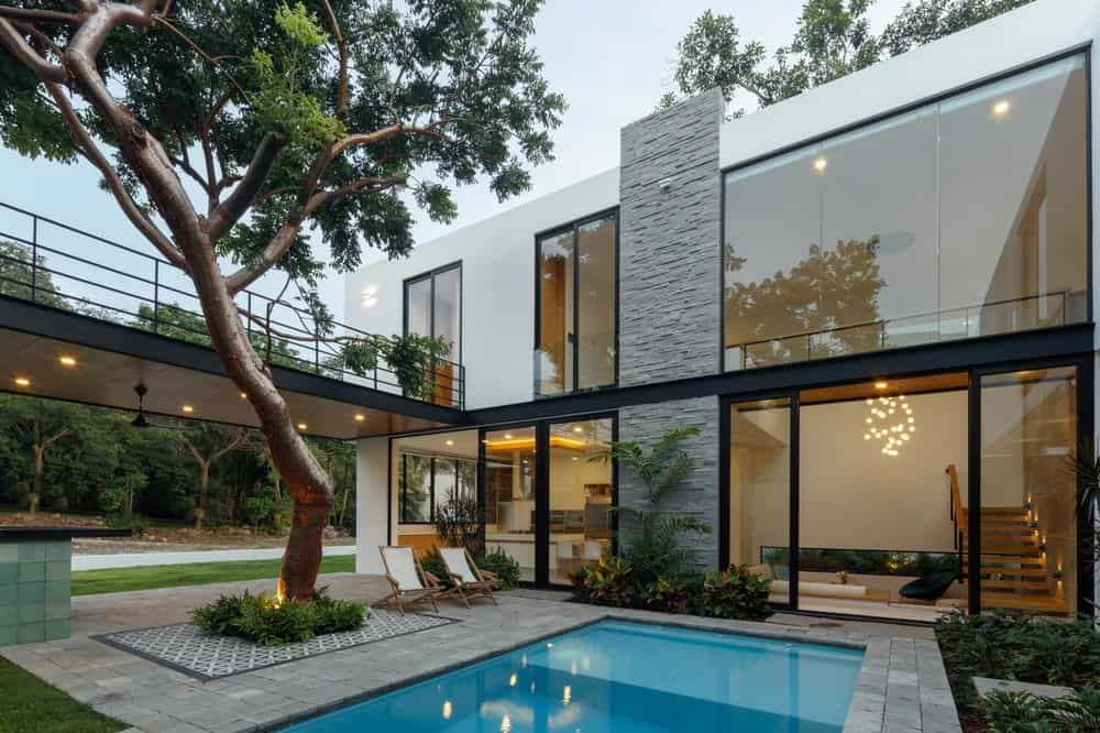 The glass walls are complemented by the textured stone wall and the white exterior walls that support the glass structures.