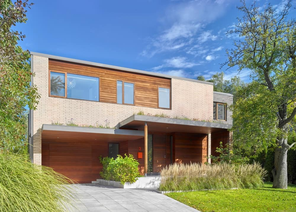 This is a front view of the house with a wide concrete driveway adorned with grass and shrubs that bring color to the wooden tones of the house.