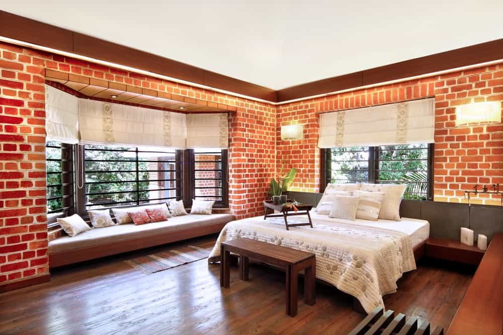 This bedroom also has a large reading nook under the large window with cushion. The red brick walls pair well with the hardwood flooring.