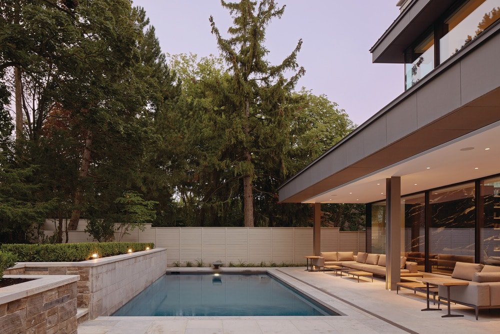 This is a look at the backyard swimming pool from the side of the lounge chairs. You can see here the tall trees of the landscape that bring shade and privacy to the poolside area.