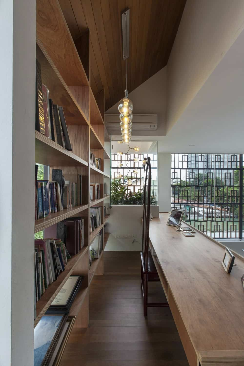 This is the home office and study area with a large wooden built-in desk that pairs well with the large wooden structure with shelves behind it.