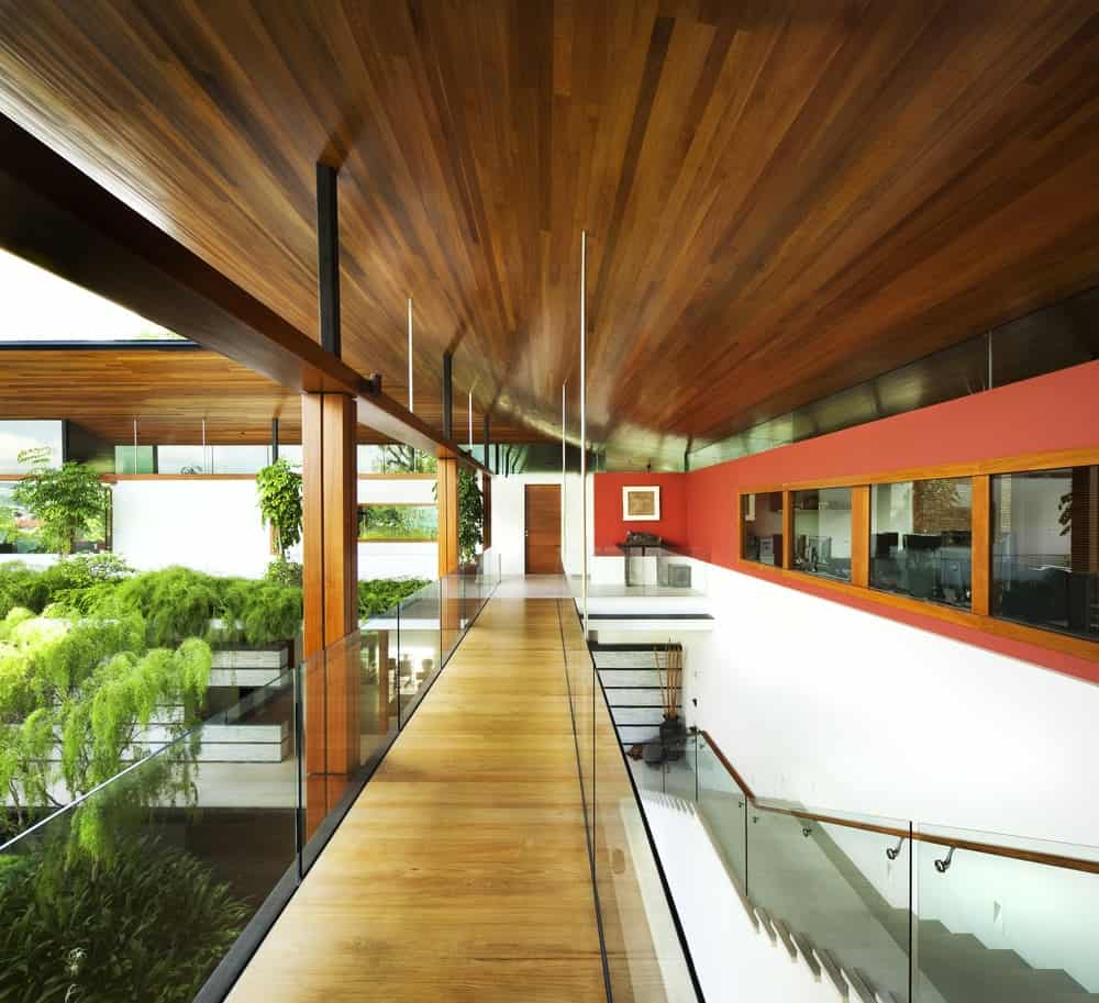 This is the second-floor landing with a long and narrow hallway of hardwood flooring topped iwth a shed wooden ceiling and has glass walls on its indoor balcony.