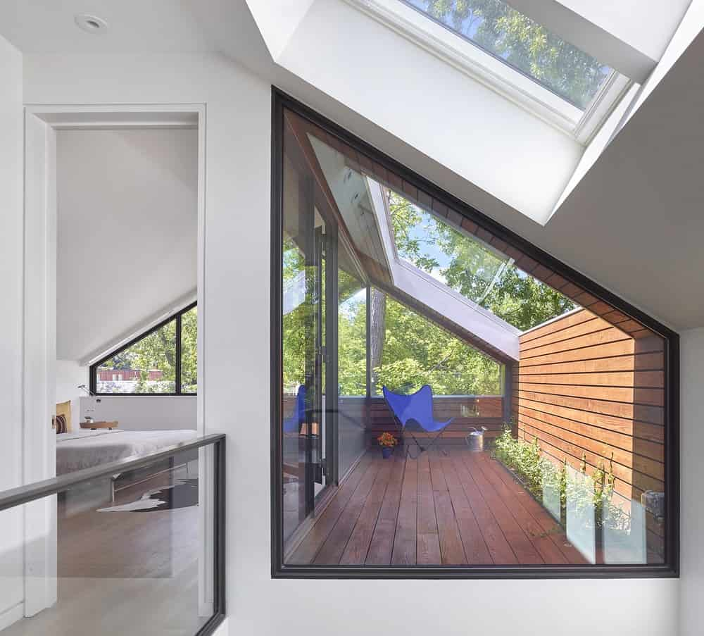 This view of the top floor showcases the small balcony surrounded by glass doors and has a wooden deck flooring.