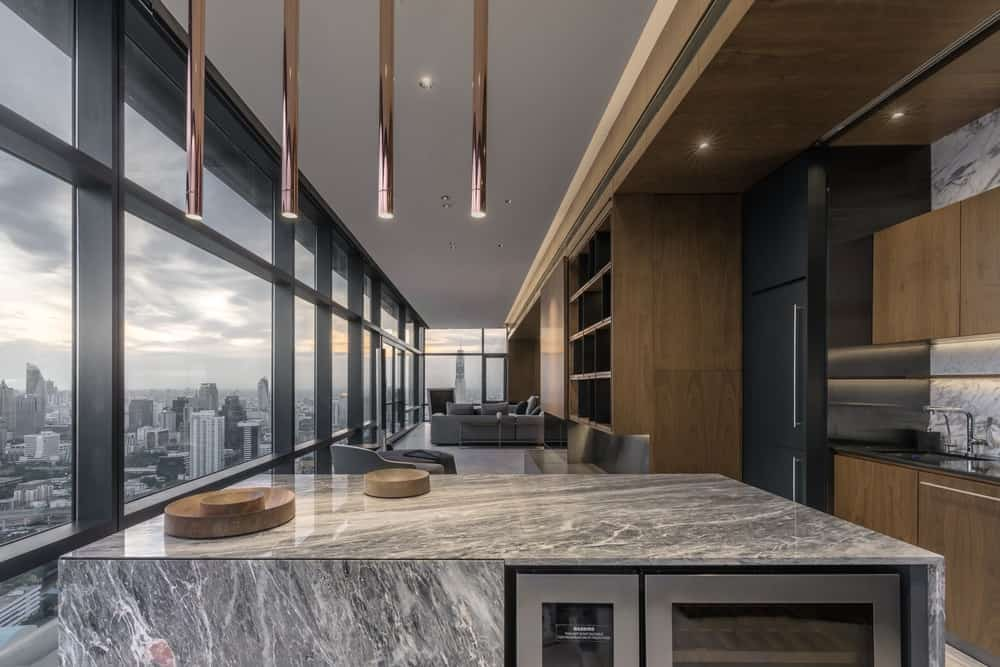 The white marble waterfall kitchen island has a built-in wine fridge.