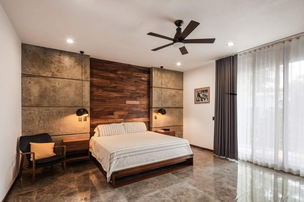 The primary bedroom has a large bed adorned by the wall behind the headboard that has a middle wooden panel flanked by concrete walls illuminated by pendant lights to serve as bedside lamps.