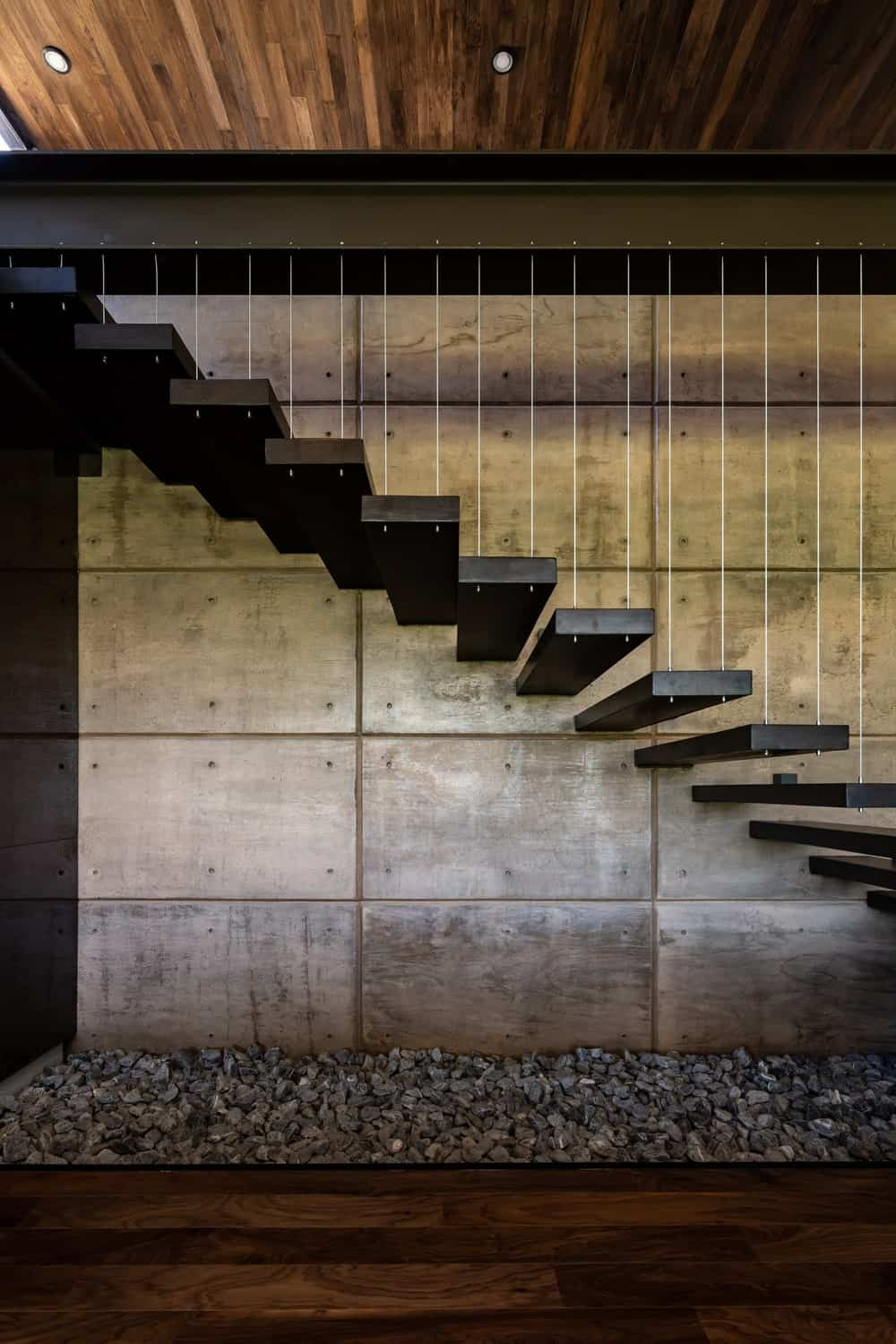 This closer look at the modern floating steps of the staircase showcases the bed of gravel underneath.