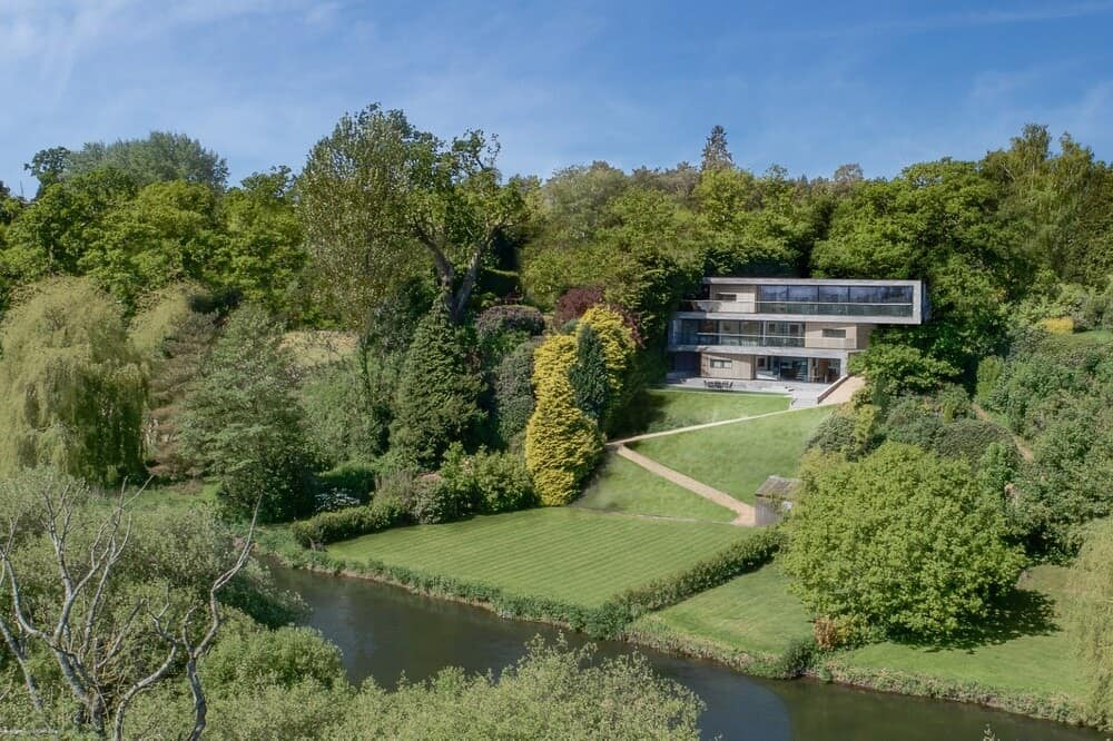 This is an aerial view of the property showcasing the glass house on top of a small hill that is festooned with tall trees.