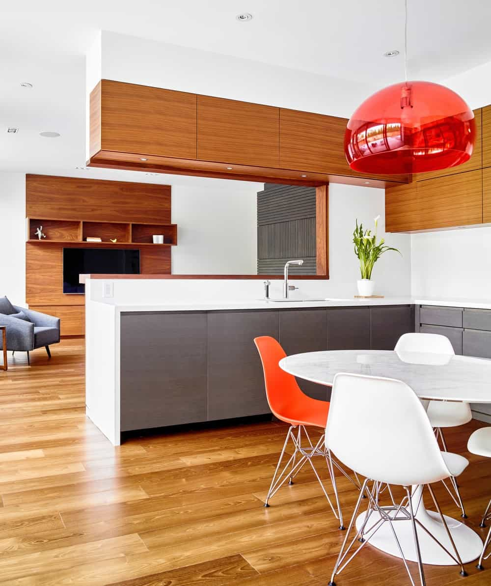 The kitchen has a bright white L-shaped peninsula with gray cabinetry. This matches well with the breakfast nook that has a white dining table paired with white modern chairs.