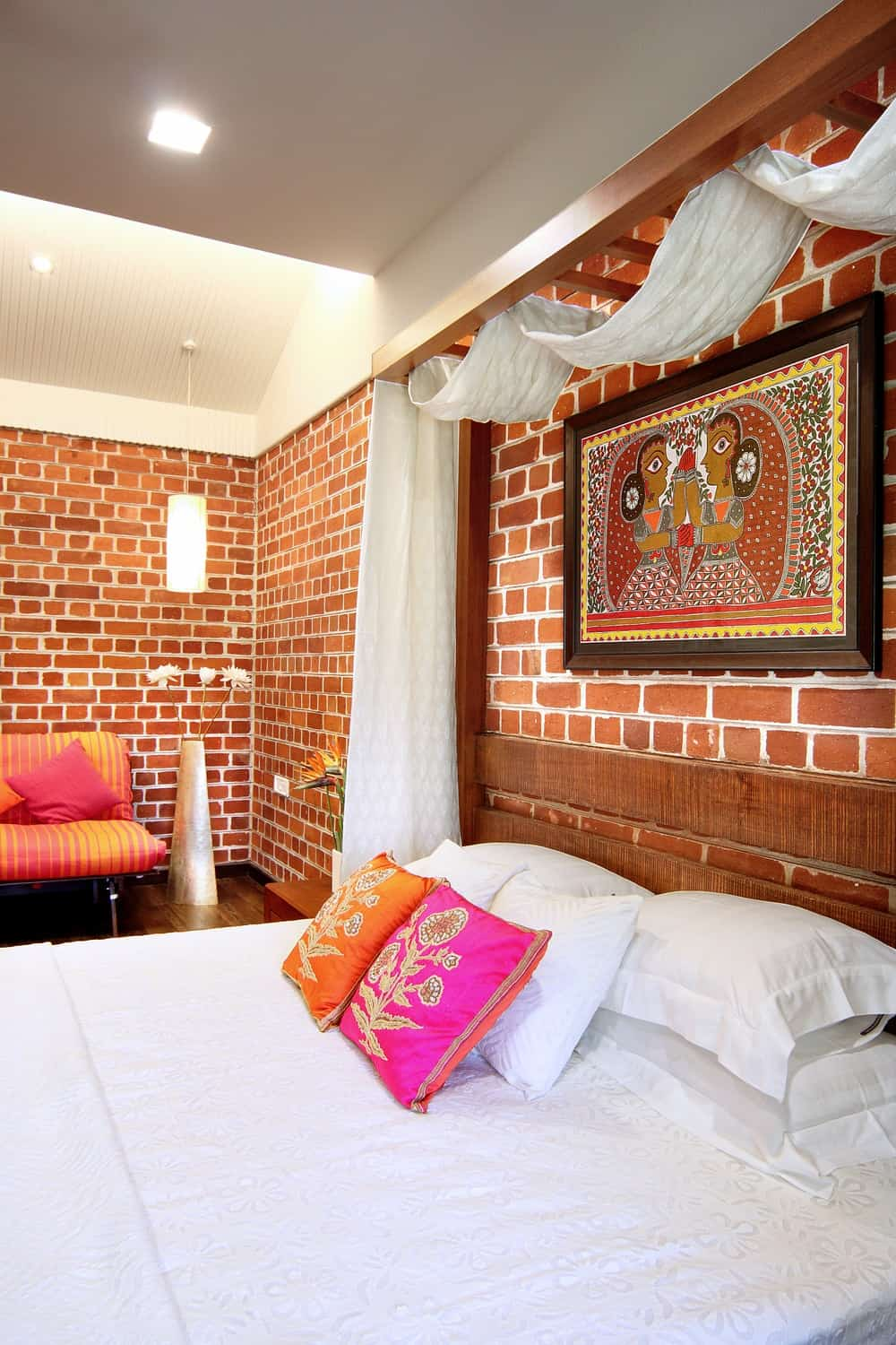 This other bedroom has a wooden bed topped with a colorful painting above its wooden headboard and has a sitting area on the side.