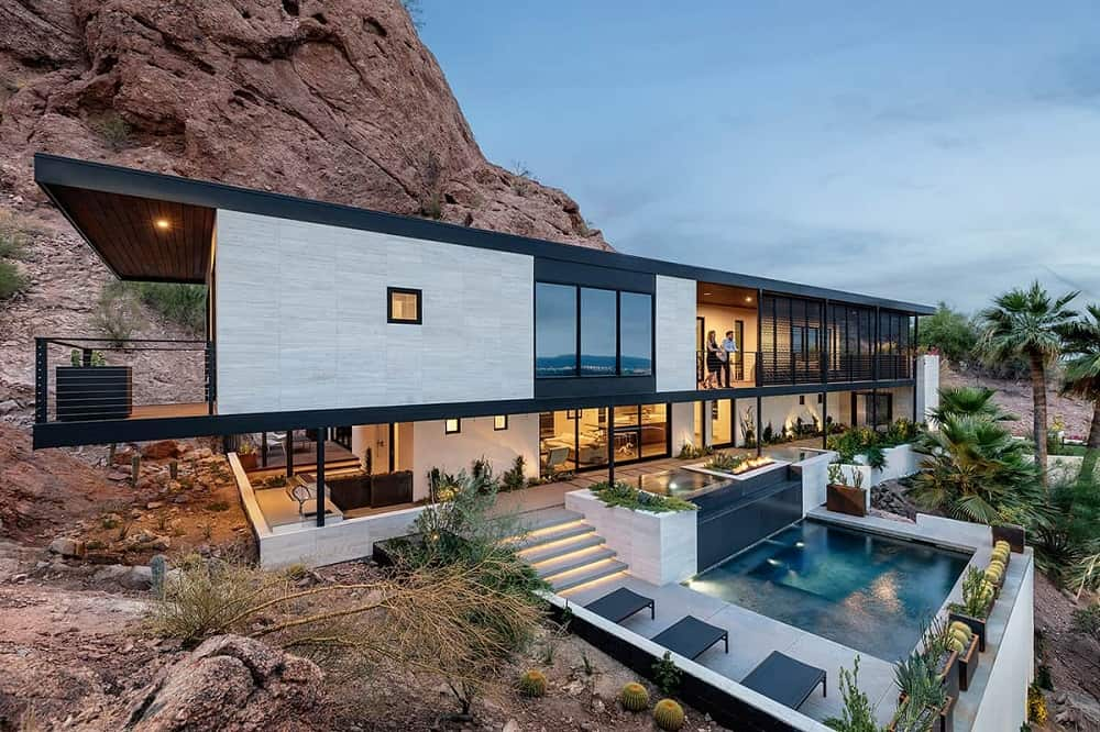 This is a view of the modern house with glass walls, balconies and windows looking out onto the pool area below. The sleek elements of the house are contrasted by the surrounding landscape of red rocks and mountainside.
