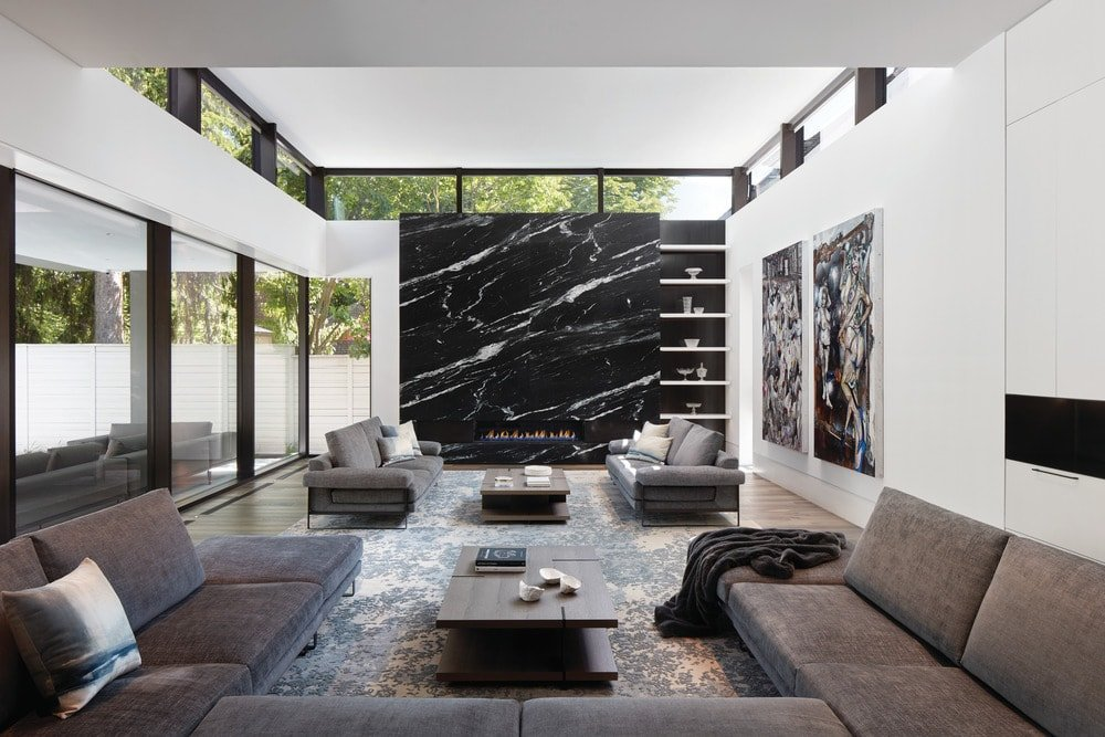 This is the spacious living room with enough room for a large U-shaped sectional sofa and a couple of sofas by the modern fireplace on the far side embedded into a large black marble panel.