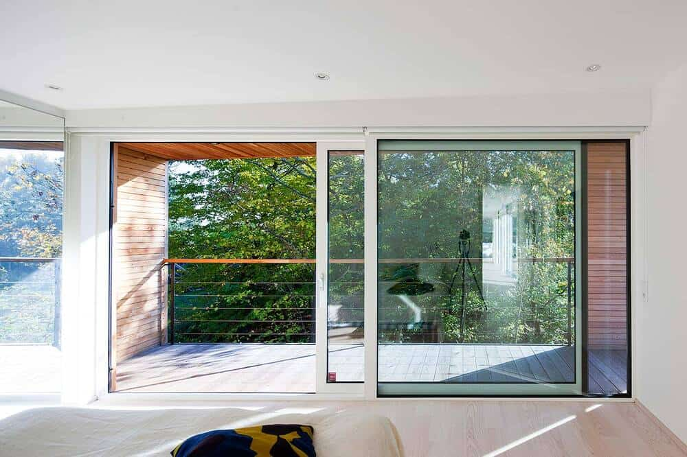 this is a look at the large sliding glass doors that open to the balcony adorned by the landscape beyond.