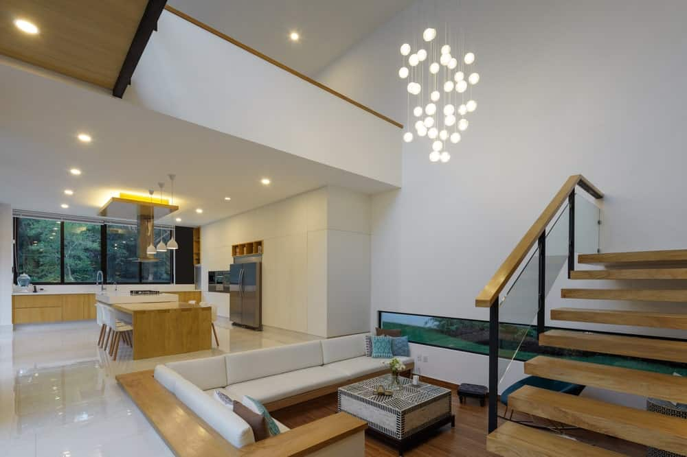 This is the conversation pit that is topped with a set of small decorative lights hanging from the tall ceiling.