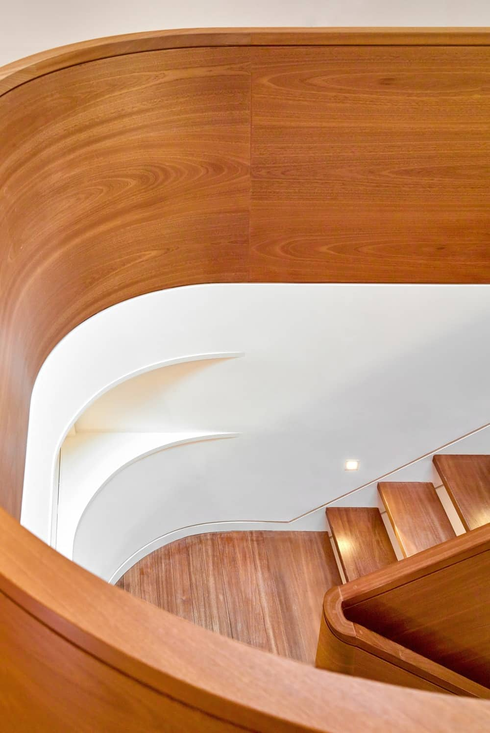 This is a look down the wooden stairs from the second level. You can see here the wooden steps complemented by the white walls.