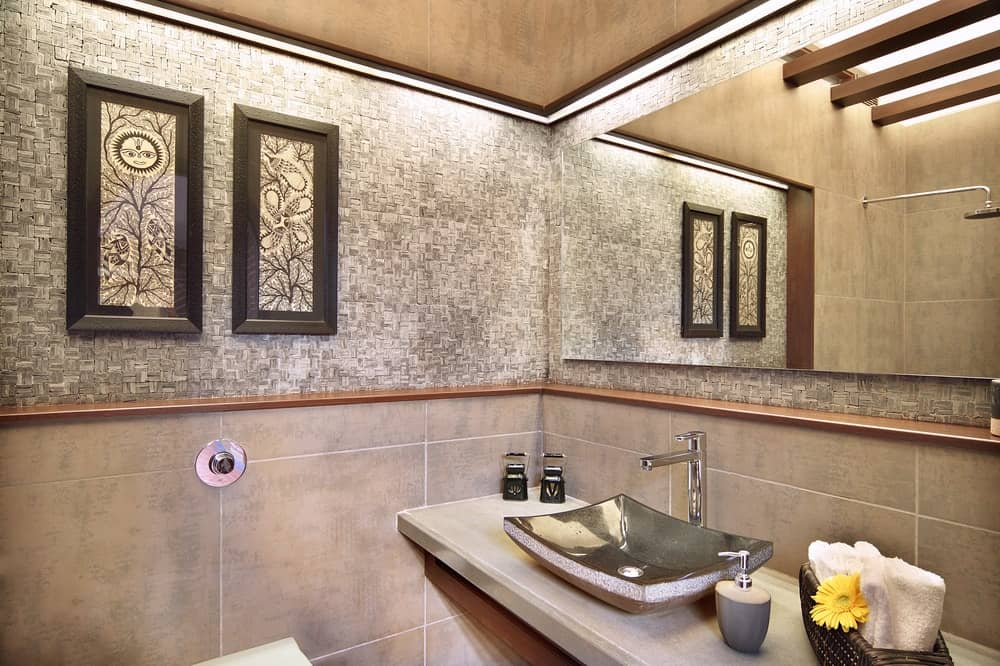 The bathroom has an earthy gray tone to its tiles and walls. It also has a floating vanity with freestanding sink below a large glass mirror.