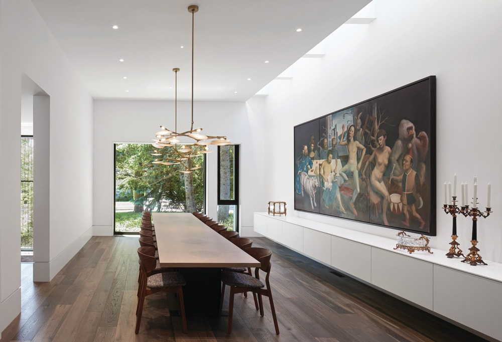 This is the large formal dining room with a long rectangular wooden dining table surrounded by wooden chairs that match the hardwood flooring. These are then complemented by the large painting on the wall.