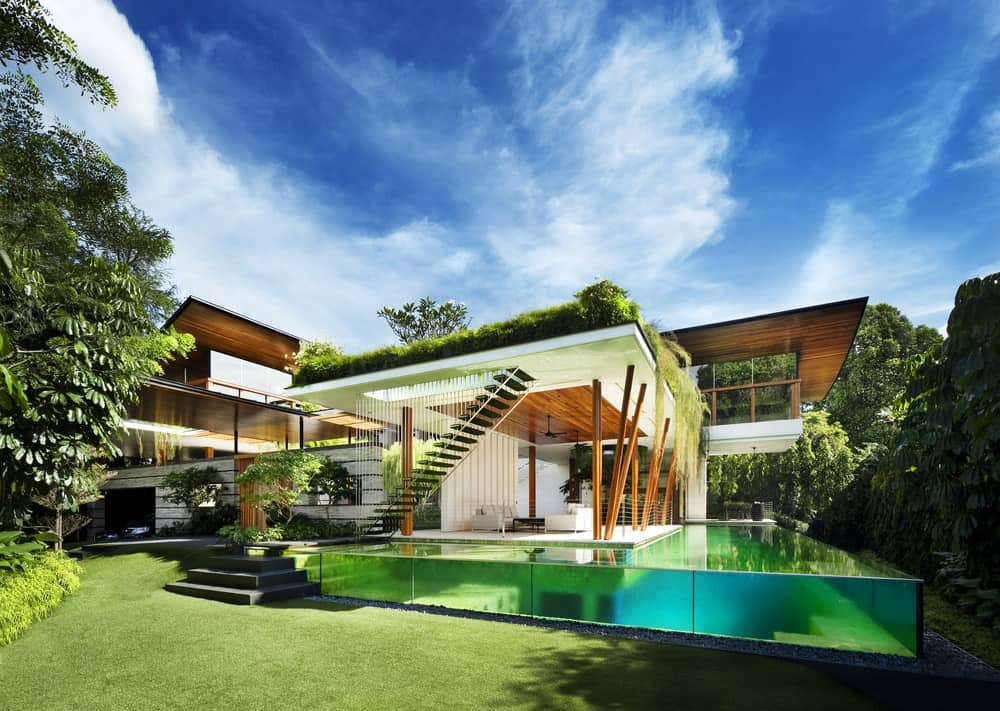 This is an exterior view of the side of the house showcasing the glass walls of the infinity-edge pool attached to the house that has a lot of outdoor areas with open walls.