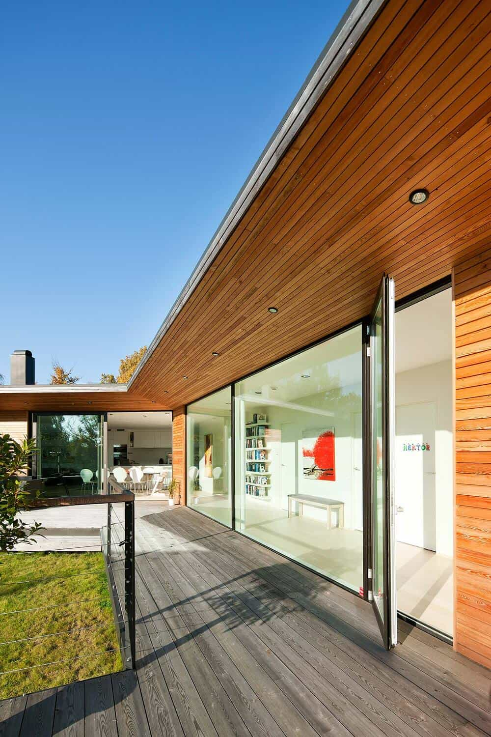 The elevated wooden deck patio that runs on the side of the house is topped with a wooden ceiling and wall that makes the glass wall stand out.