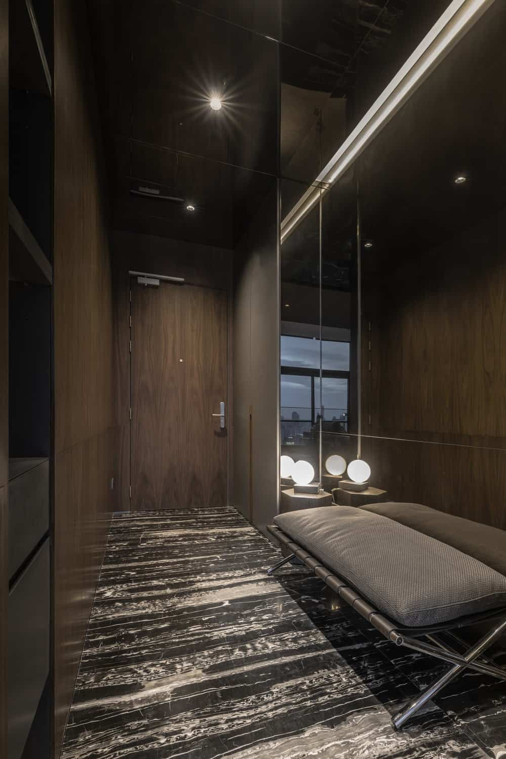 This is the hallway leading to the bathroom with a gray sofa on the mirrored wall.