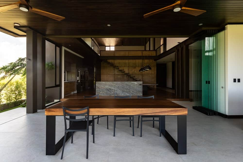 This wooden dining table is topped with a wooden shiplap ceiling with recessed lights and ceiling fans.