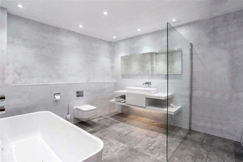 This other bathroom has the same deisgn with its floating vanity and toilet across from the large bathtub. These are then complemented by the surrounding light gray tones.
