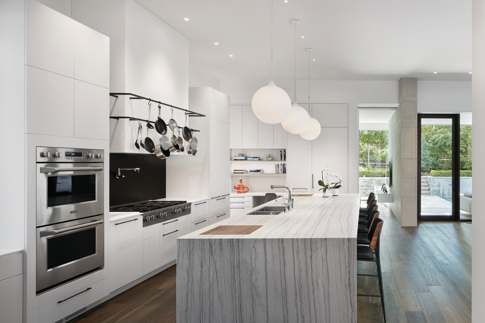 The kitchen has a white marble waterfall kitchen island topped with spherical pendant lights. Across from this is the bright cabinetry that makes the appliances stand out.
