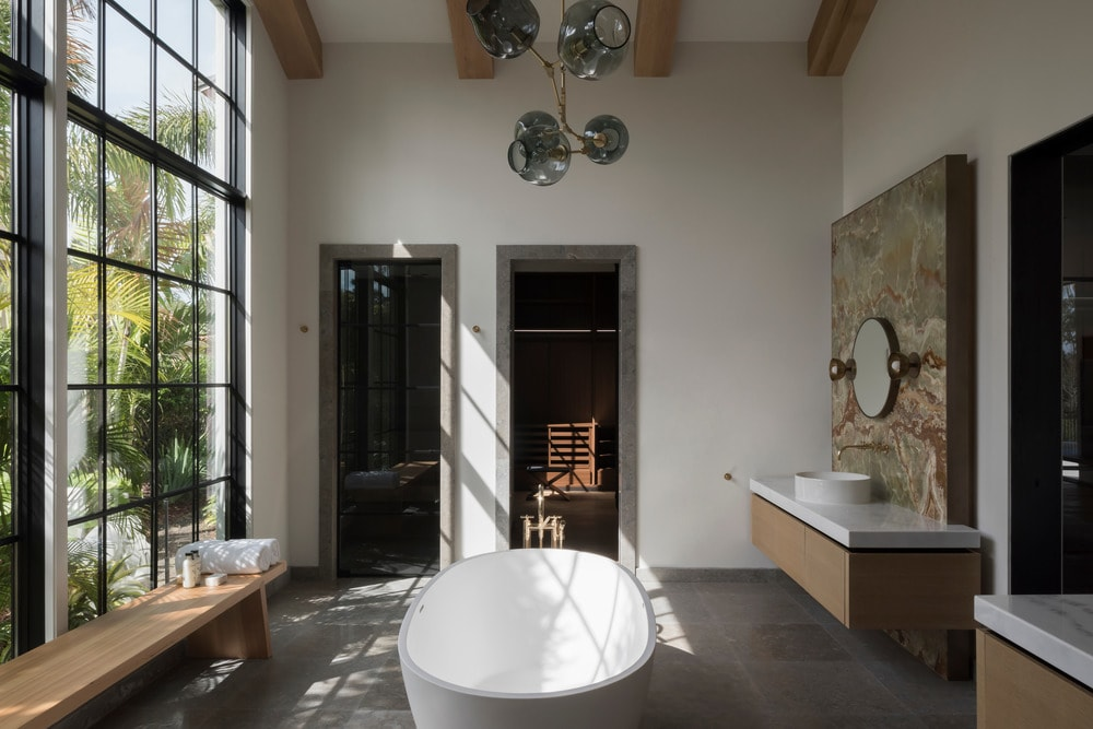 This is the spacious bathroom with a large freestanding bathtub in the middle. Across from this are two floating sinks flanking the door and opposite is a large window with a wooden bench.