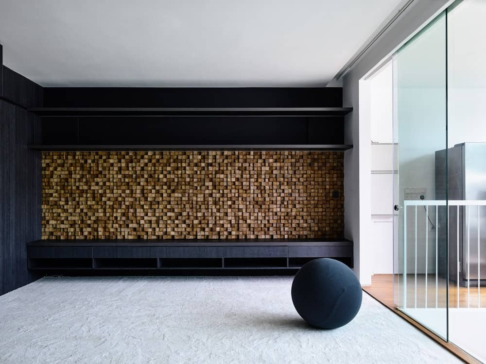 This part of the house has a textured wooden wall with black wooden structures on the sit and floating shelves above that resembles a mudroom. These are then brightened by the glass wall on the side.