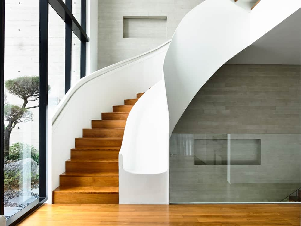 This curved staircase has white walls on both side of the steps that contrast the wooden tone of the steps.