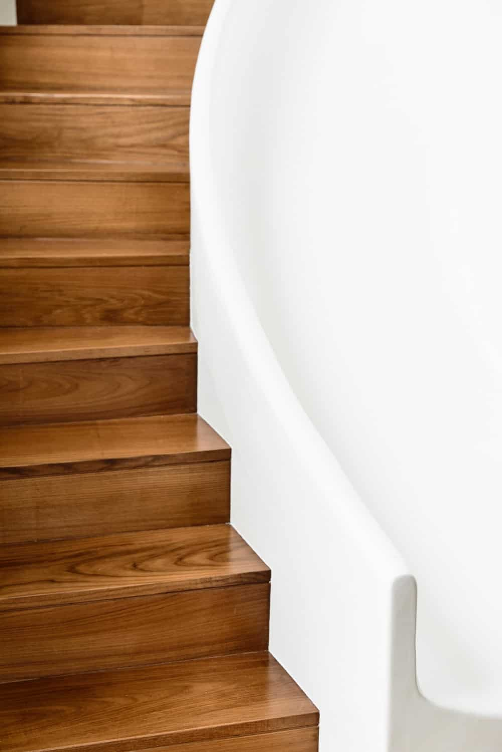 This close look showcases the contrast between the wooden steps with the white wall railing.