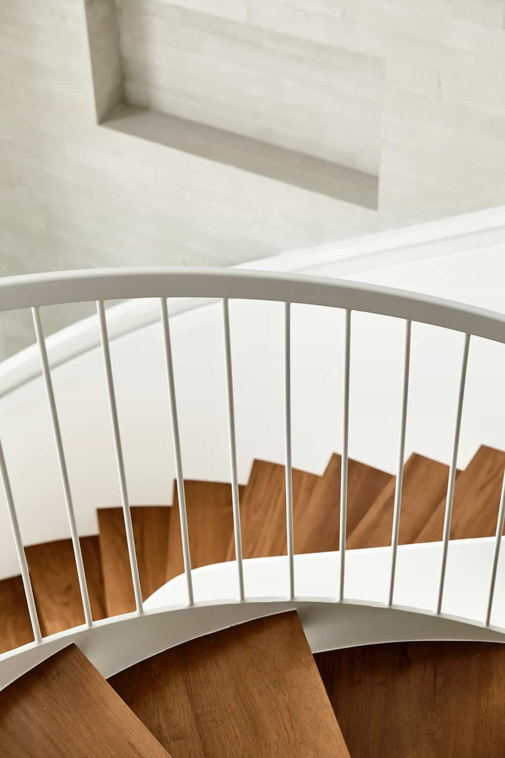 The spiral staircase above has thin white railings on its side contrasted by the wooden steps.