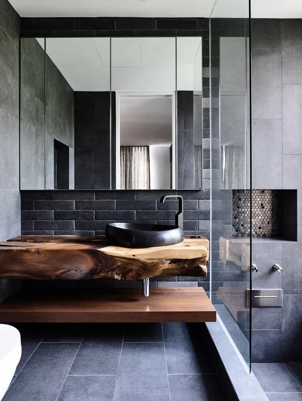 This bathroom has a black freestanding sink on a rustic slab of wood matched with the black brick backsplash.