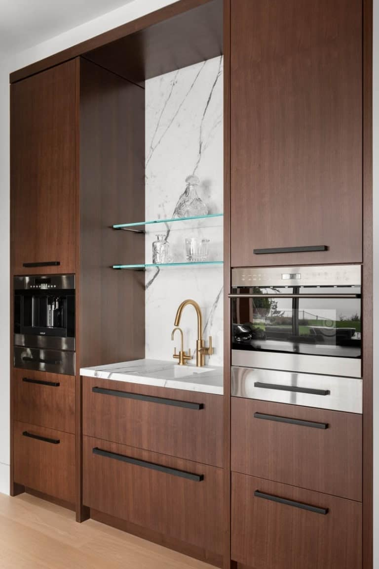This is a close look at a dark wooden kitchenette with a small sink and an oven that stands out against the dark wooden cabinetry.