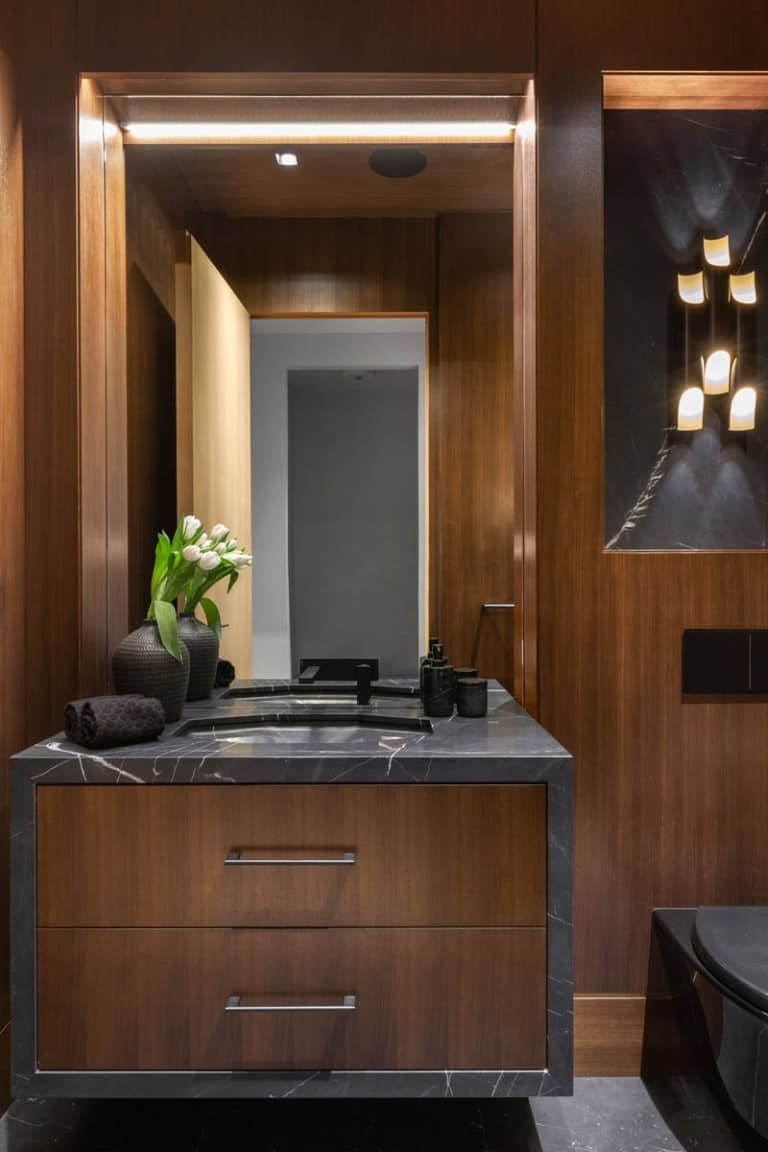 This is the powder room with wooden elements accented by the dark marble countertop that matches with the toilet.