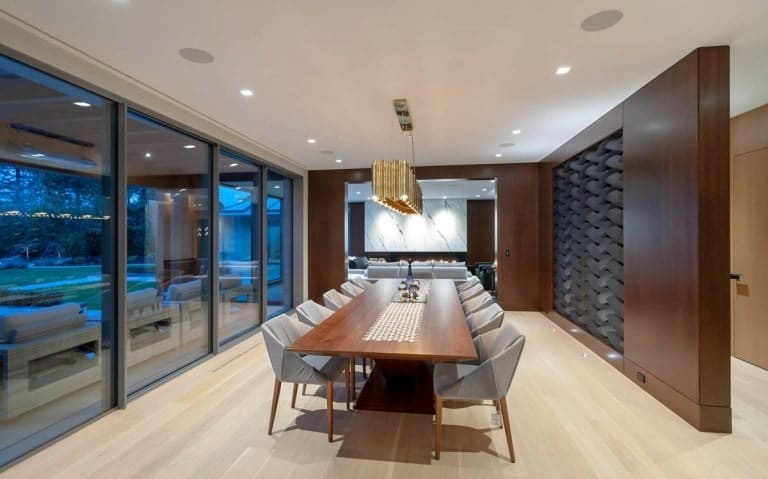 This is another view of the formal dining room showcasing the surrounding gray chairs and the light hardwood flooring.