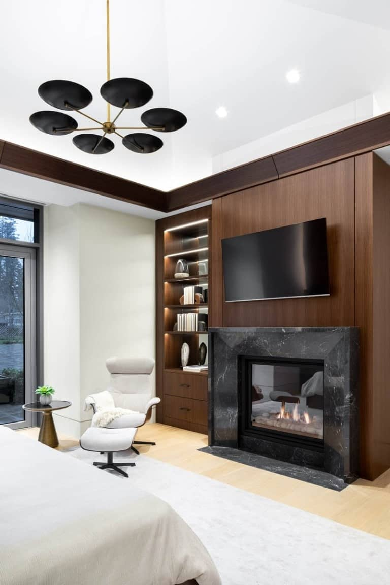 Across from the foot of the bed is the fireplace with a dark marble mantle topped with a wall-mounted TV and has a built-in shelving on the side.