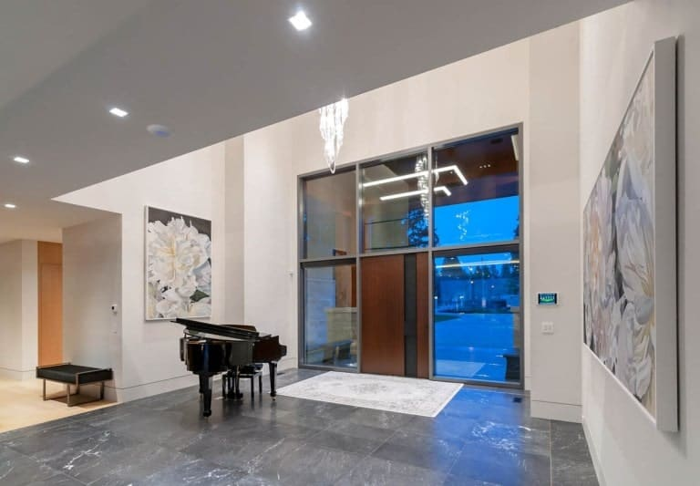 Upon entry of the house, you are welcomed by this foyer with a grand piano and large glass panels surrounding the main door.