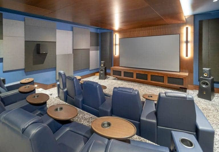 This is a look at the home theater room with rows of gray leather theater seats across from the large screen.