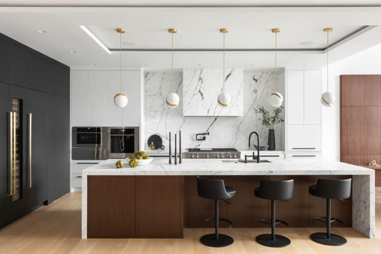 This is the kitchen with a large waterfall white kitchen island contrasted by its dark brown cabinetry and black modern stools.