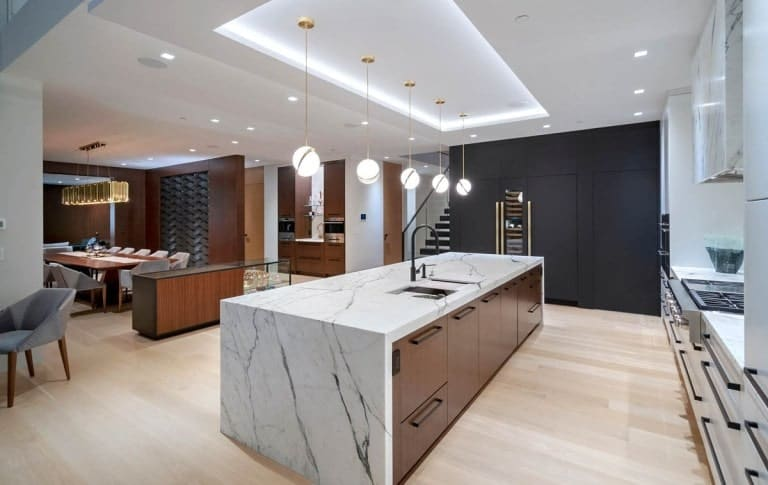 This is a closer look at the white marble waterfall kitchen island topped with pendant lights from a tray ceiling.