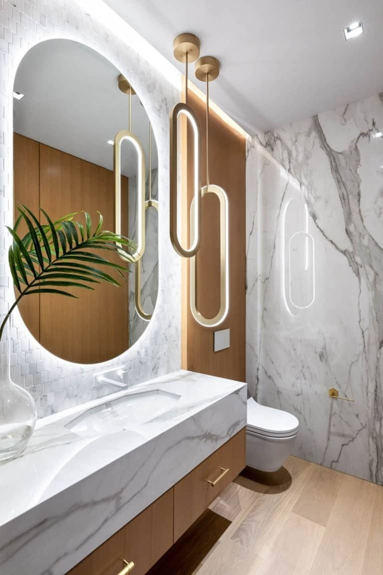 This bathroom has a consistent white marble tone to its walls and vanity area that has a mirror that matches with the modern pendant lights.