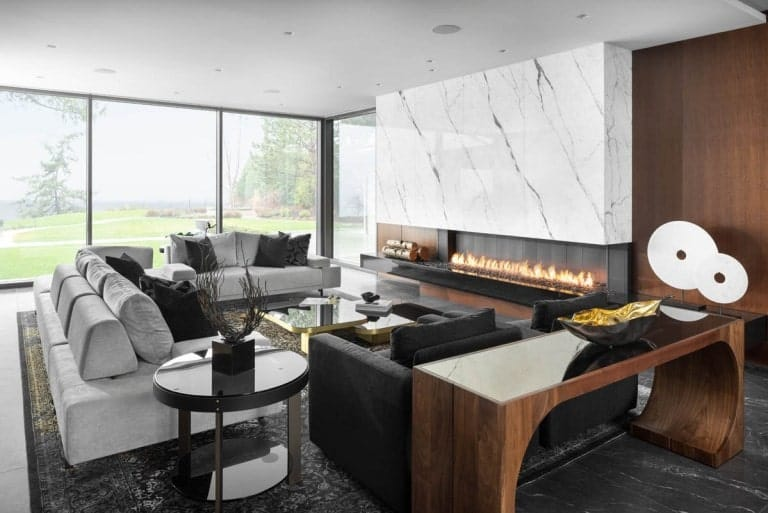 This living room has white sofas and black amrchairs across from the modern fireplace within a large white marble wall.