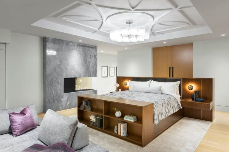 This other bedroom also has a built-in wooden bed with shelves and bedside drawers. On the side of this is a modern fireplace.