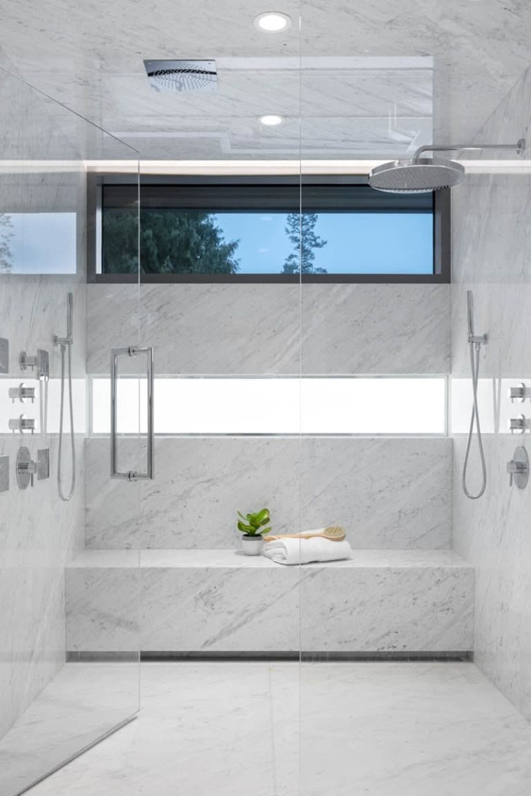 This is a glass-enclosed shower area with the same white marble tone on its walls.