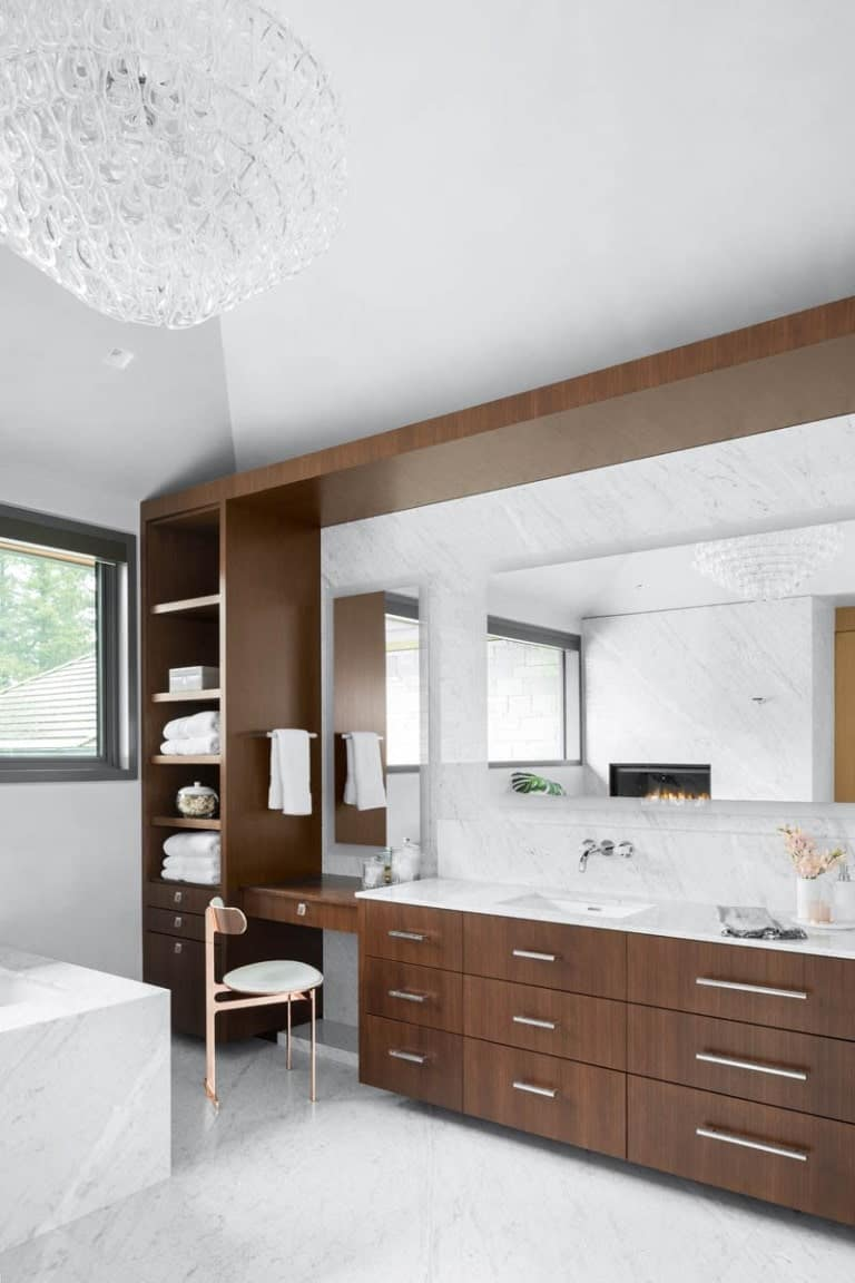 This is a look at the large wooden structure of the bathroom that has a vanity, a sink area and built-in shelves.