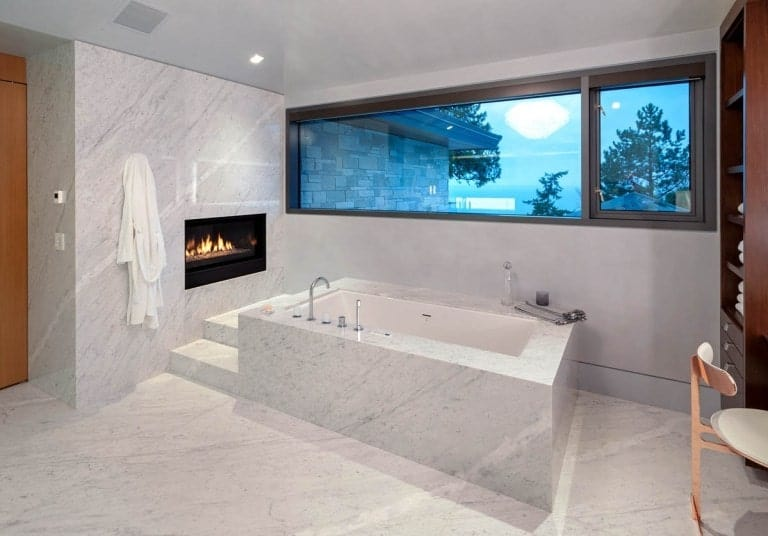 This bathroom has a large white marble bathtub with its own fireplace.