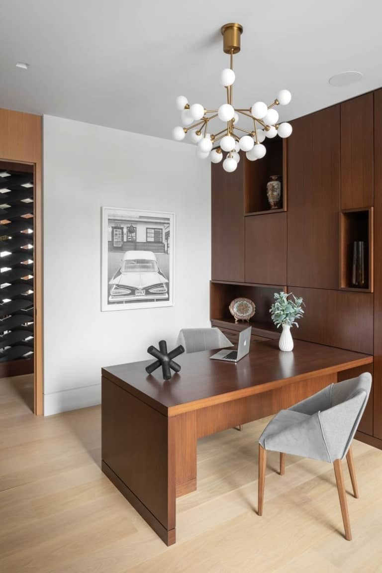 This is the home office with a large wooden built-in desk that blends well with the wood-paneled wall that has built-in shelves.