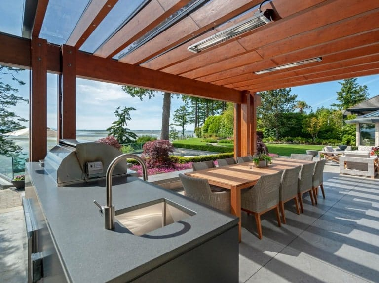 This is a covered patio with an outdoor dining set and a grilling station under a set of trellises.