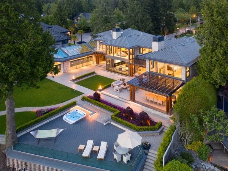 This is an aerial view of the house that glows warmly from the interior lights that spill out of the glass walls.