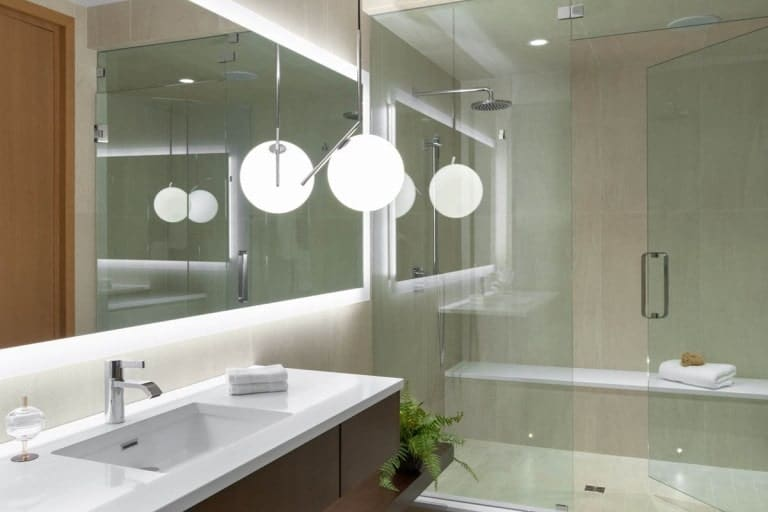 This bathroom has a white modern vanity topped with a large mirror with a back-lighting. On the side is the glass-enclosed shower area.